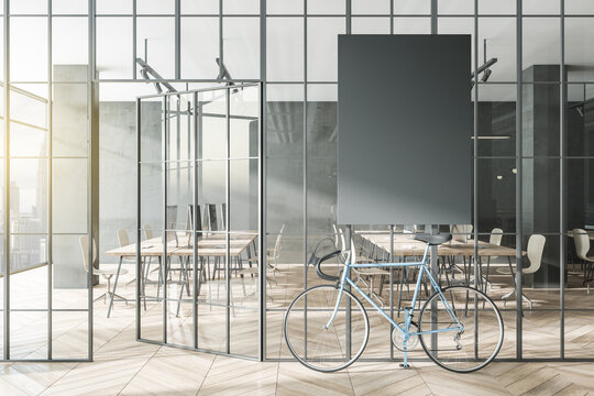 Contemporary glass partition and bike in stylish coworking office interior with empty black mock up poster and city view and daylight. 3D Rendering.