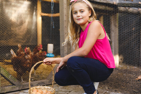 Portrait of smiling caucasian girl collecting eggs from hen house in garden