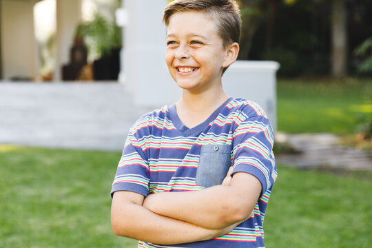 Smiling caucasian boy outside house looking away from camera in garden