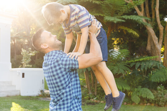 Smiling caucasian father lifting his son up outside house in sunny garden