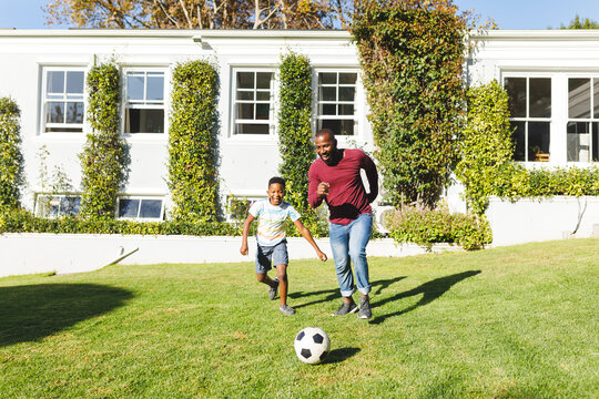African american father with son having fun and playing football in garden