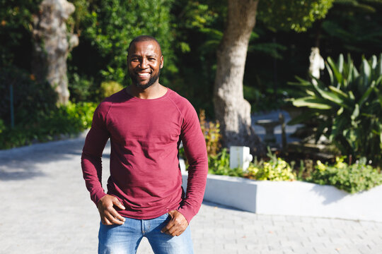 Portrait of african american man smiling and looking at camera in sunny garden