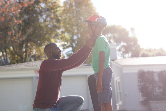 African american father with son smiling and preparing before skateboarding in sunny garden