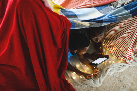 Happy african american father and son lying in blanket fort, using tablet