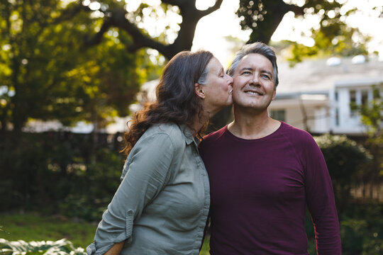 Happy senior caucasian couple kissing and smiling in garden