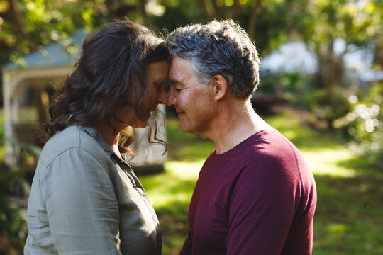 Happy senior caucasian couple embracing and smiling in sunny garden