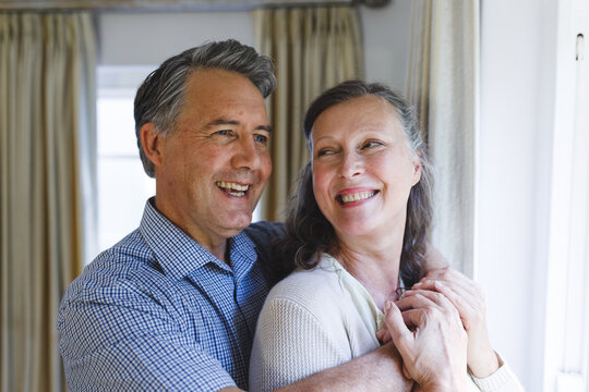 Happy senior caucasian couple standing next to window, embracing and smiling