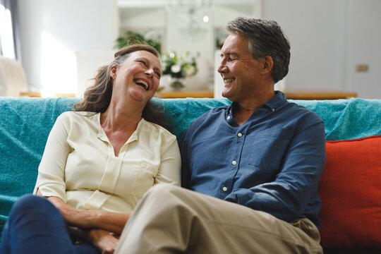 Happy senior caucasian couple in living room sitting on sofa, smiling