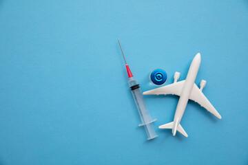 Obraz Covid air travel background. Airplane with a coronavirus vaccine needle - fototapety do salonu
