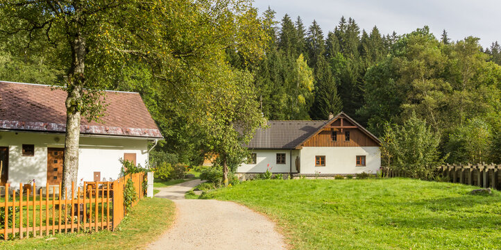 Panorama of a walking path and traditional houses in the Sumava mountains, Czech Republic