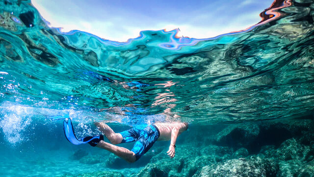 Man snorkeling in the blue sea on a sunny day in Sardinia