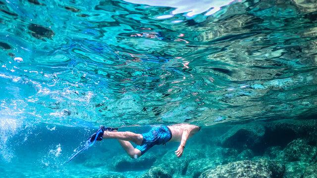 Man snorkeling in the blue sea in Sardinia