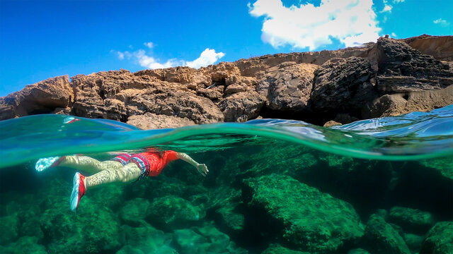 woman swimming in the blue sea by the rocky shore