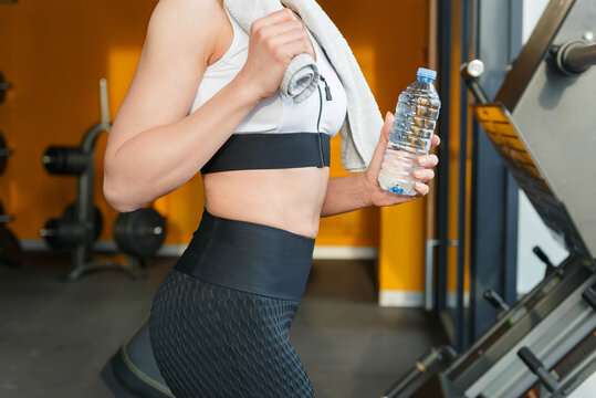 Fitness woman with towel around her neck band and water bottle. eck.