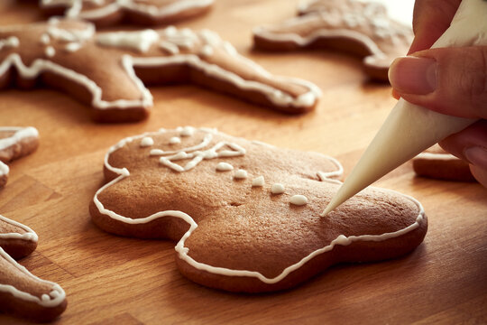Decorating homemade gingerbread Christmas cookies with white icing using a cone