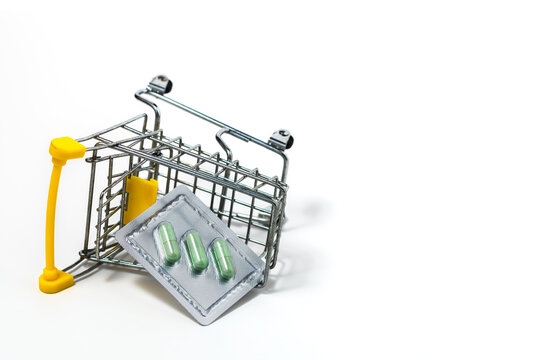 Green chiretta herbal capsule in the shopping cart against white background for healthcare and medical concept