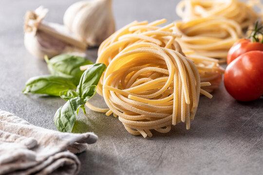 Italian pasta nest, basil, garlic and tomato. Uncooked spaghetti nest