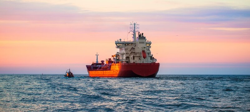 Large cargo ship sailing at sunset. Baltic sea. Panoramic view. Freight transportation, logistics, global communications, economy, business, industry