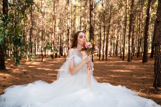 Bride with white wedding dress in forest holding colorful and dried wedding bouquet.