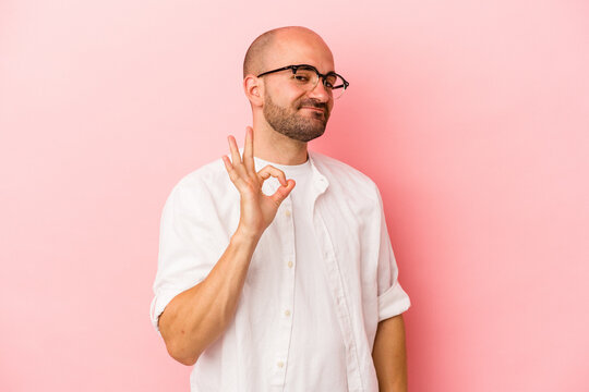 Young caucasian bald man isolated on pink background  winks an eye and holds an okay gesture with hand.