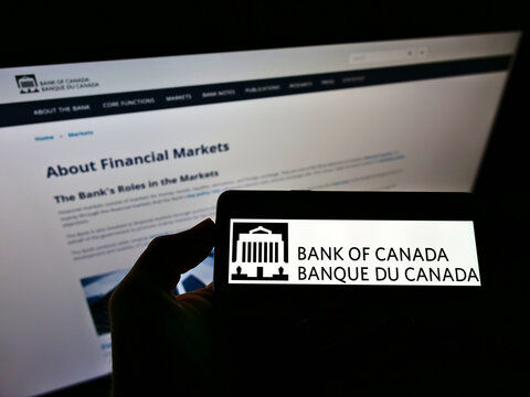 STUTTGART, GERMANY - Jun 01, 2021: Person holding mobile phone with logo of Bank of Canada (BOC) on screen in front of web page.