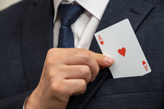 Ace card in the hand of a businessman in a suit.