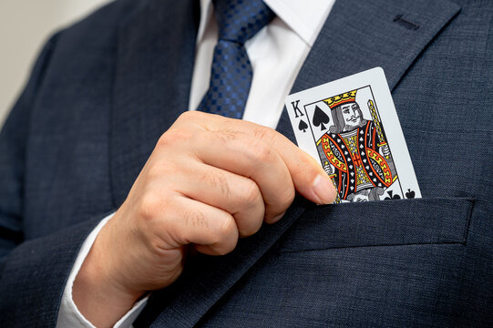 Poker king card in the hand of a business man in a suit.