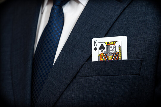 A poker king card in the pocket of a suit.