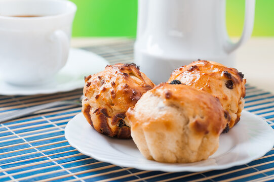 Small muffins on plate, jug of milk and cup of tea on blue bamboo table cloth.
