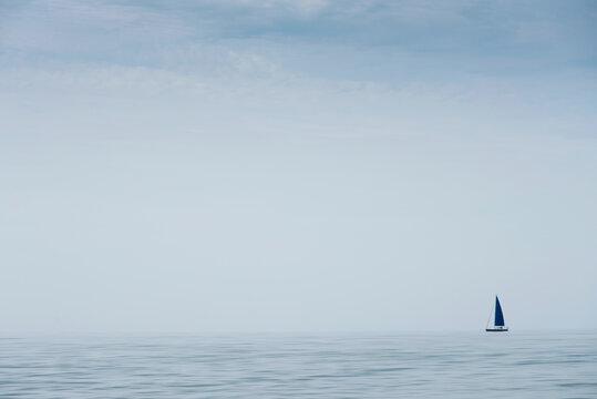 sailboat sails over the sea in a peaceful blue landscape
