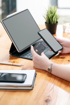 Hands holding plastic credit card and using mobile phone. Online shopping concept.