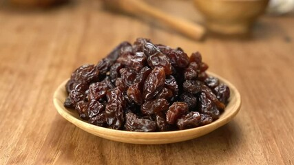 Fototapete - Zoom in scene pile of dried sweet raisins in wooden dish on wooden table.