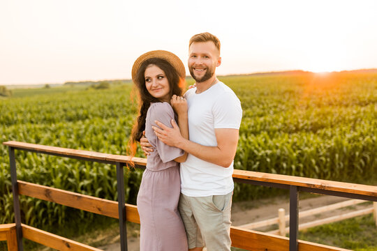 Charming smiling man gently hugging attractive woman, enjoying happy moments. Joyful beautiful young couple spending weekends together outdoors, standing at the field, cuddling, romantic date concept