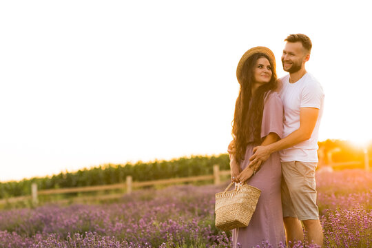 Joyful stylish couple standing at the lavender field, smiling, having a romantic date in the sunset. Handsome man gently hugging pretty woman with picnic basket, spending weekend outdoors concept
