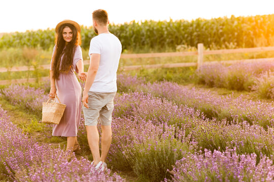 Gorgeous stylish woman with picnic basket taking a hand of charming man, walking at the lavender field, having a date. Beautiful young adult couple spends weekends together, enjoying happy moments