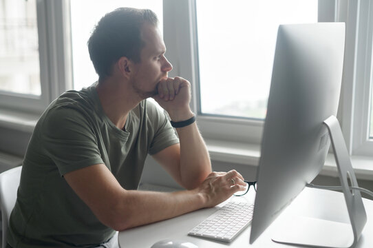 Pencive intelligent young man in casual t-shirt sits at the desk with trendy PC and looks away lost in thoughts. A freelancer takes a break and thinking about solving business tasks