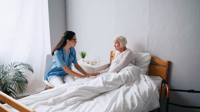 brunette nurse in eyeglasses and senior woman with grey hair talking in clinic