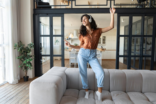 Young Caucasian woman in wireless headphones listening to music and dancing on sofa to favorite song at home, copy space
