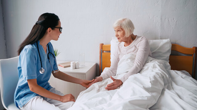 geriatric nurse in eyeglasses talking with aged woman in bed