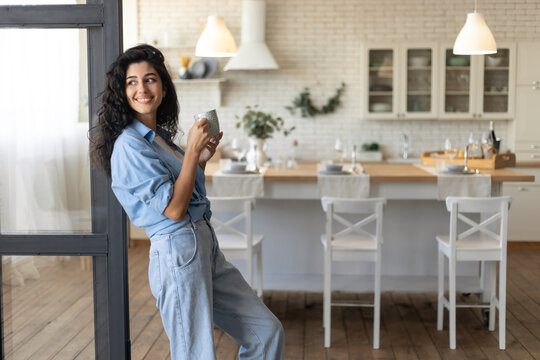 Beautiful young lady relaxing with cup of coffee at home, copy space