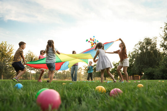 Group of children and teachers playing with rainbow playground parachute on green grass, low angle view. Summer camp activity