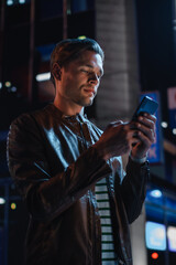 Handsome Young Man Using Smartphone Standing in the Night City Street Full of Neon Lights. Smiling Stylish Blonde Male Using Mobile Phone for Social Media Posting. Vertical Portrait Shot.