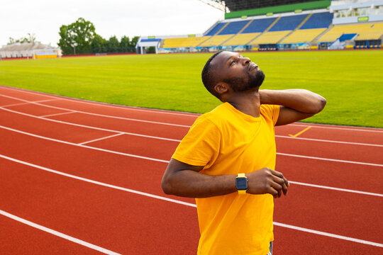 Attractive male runner standing at the stadium track, doing little warm up before training, stretching neck and shoulders. African american athlete in yellow sportswear exercising outdoors concept