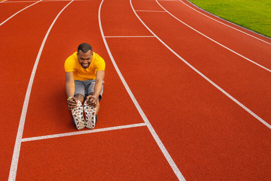 Athletic male in yellow sportswear sitting at the stadium track, doing a warm up before running, stretching legs. Concentrated african american man training outdoors, healthy lifestyle concept