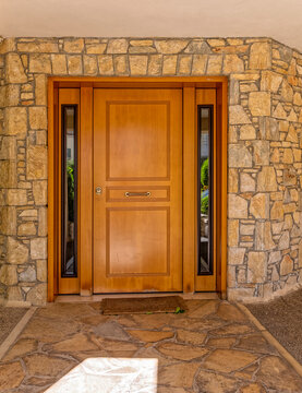 contemporary house front entrance natural wood door and stone wall