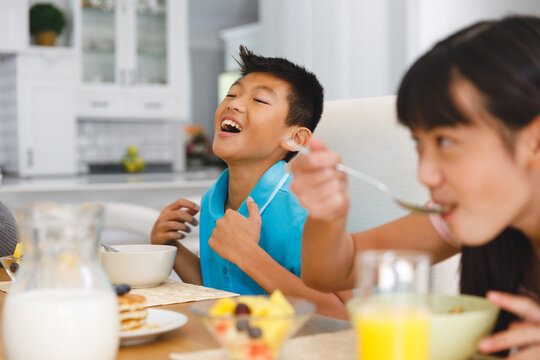 Laughing asian brother sitting at breakfast table with sister eating