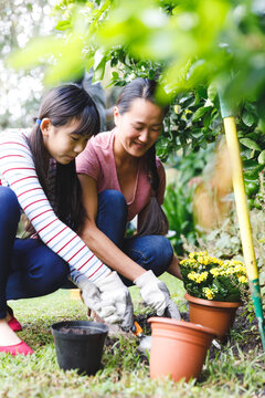 Happy asian mother and daughter smiling, wearing gloves and working in garden