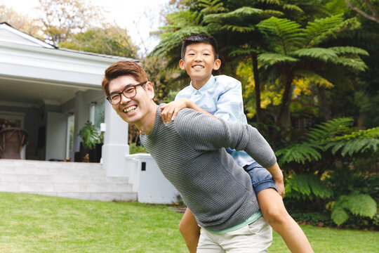 Portrait of happy asian father carrying his son and smiling outdoors in garden
