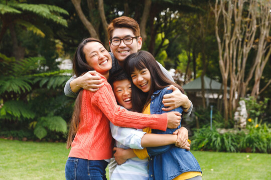 Portrait of happy asian parents, son and daughter smiling outdoors in garden