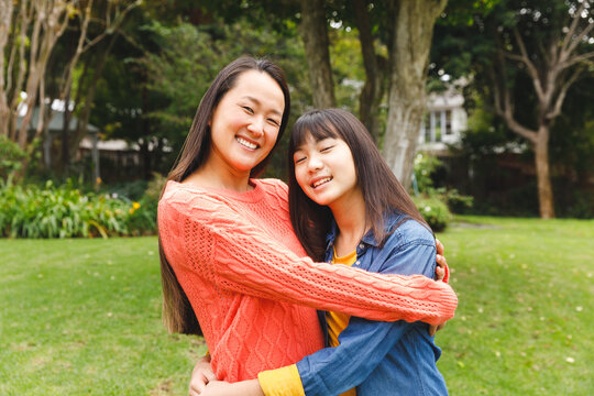 Portrait of happy asian mother embracing her daughter and smiling outdoors in garden